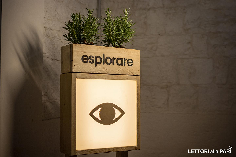 """Foto di allestimento del MAT con la scritta """"Esplorare"""", il disegno di un occhio e un'erba aromatica"""