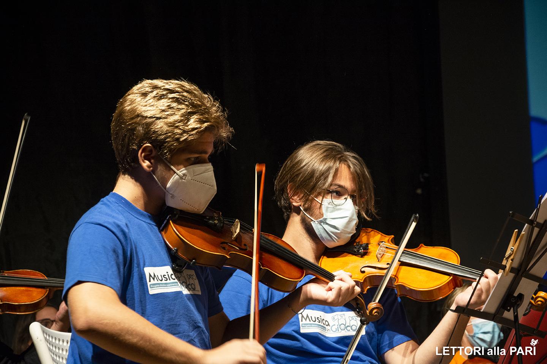 """Foto di due ragazzi durante il concerto dell'orchestra giovanile """"Musica in gioco"""""""